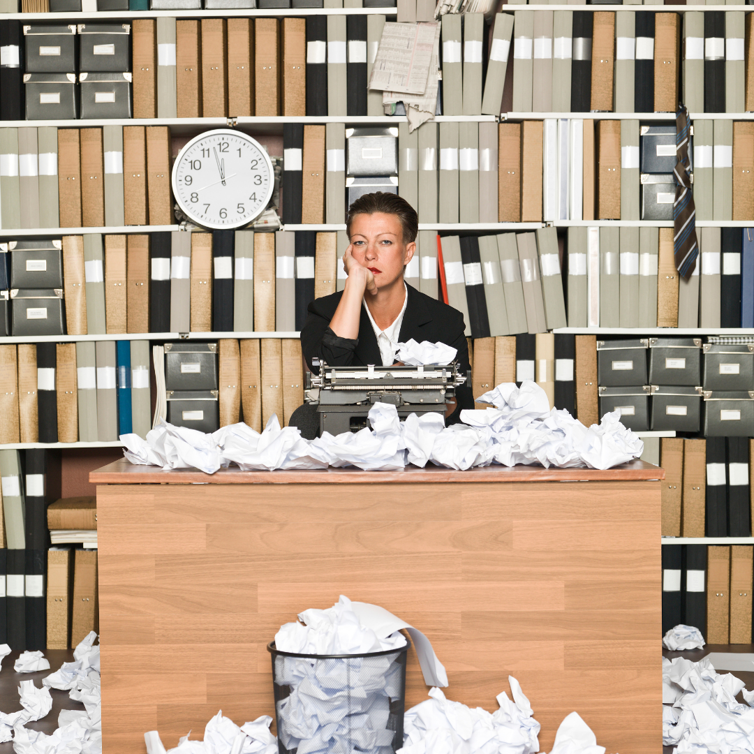 Woman at desk with wastepaper